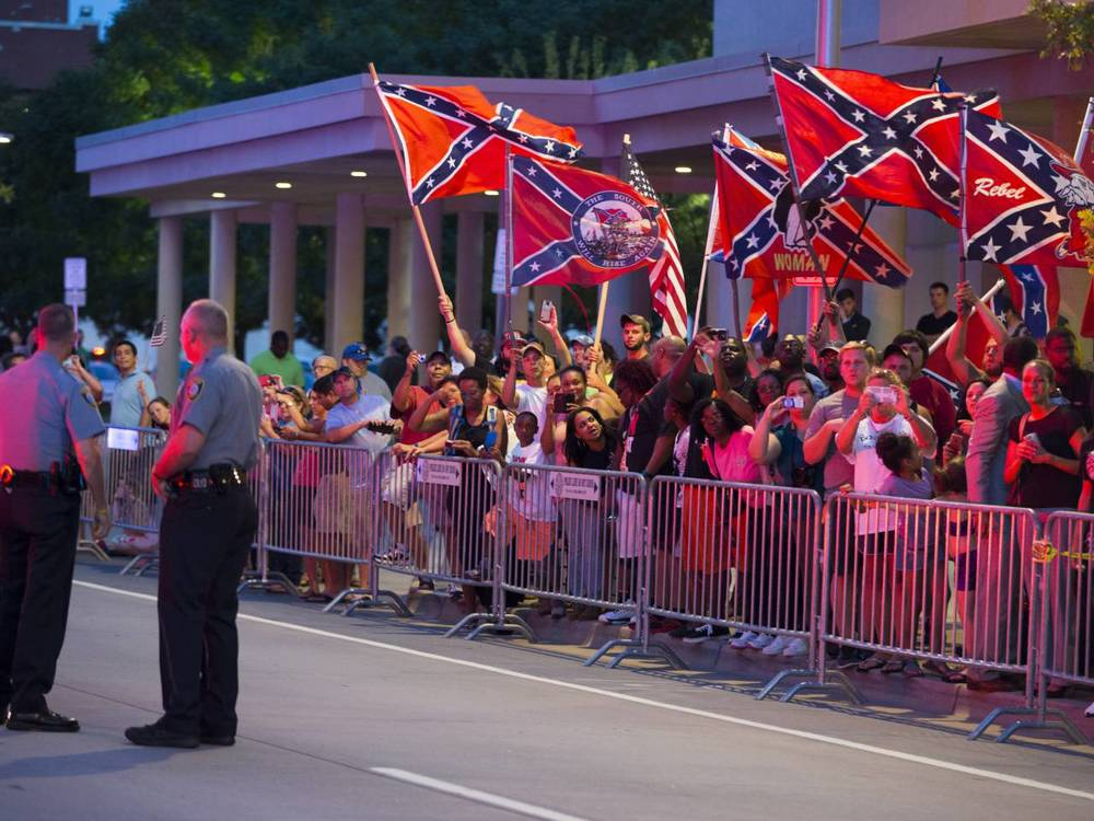 People wave Confederate flags outside the hotel that President Barack Obama is staying the night, on Wednesday, July 15, 2015, in Oklahoma City. Obama is traveling in Oklahoma to visit El Reno Federal Correctional Institution.(Credit: AP Photo/Evan Vucci)