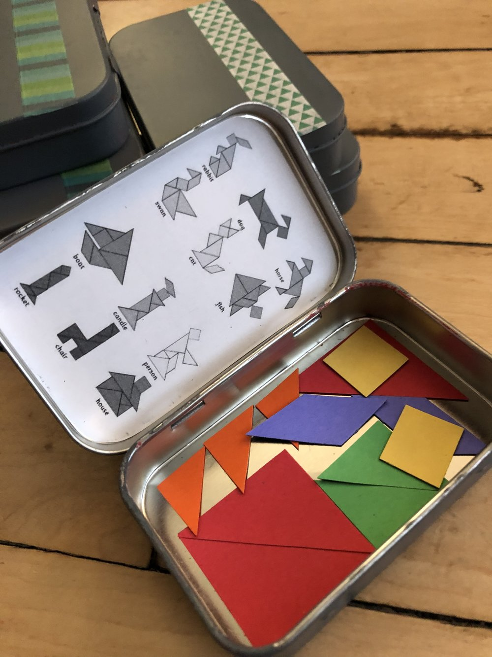 One tin contained tangrams. I used  sticky back magnet paper  to create the shapes from a simple template found  online . And on the inside of the lid printed some more common puzzles.