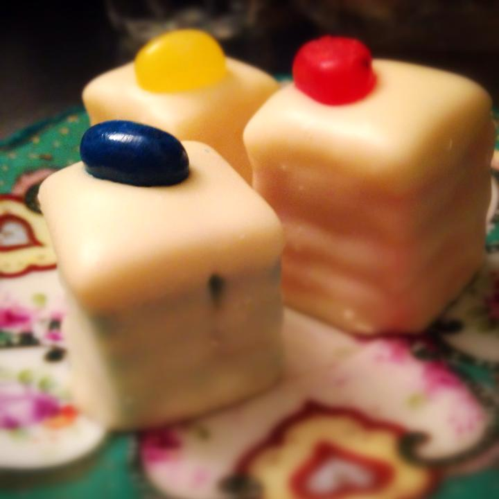 We have petit fours! Delicious layers of icing and cake covered in hard white chocolate in a variety of flavors.