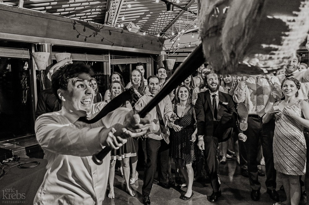The groom crushing a piñata at the reception.