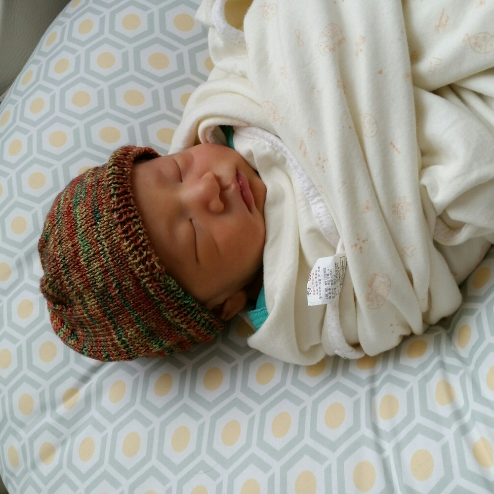 Baby Logan wearing my hand dyed Merino/Silk blend newborn hat