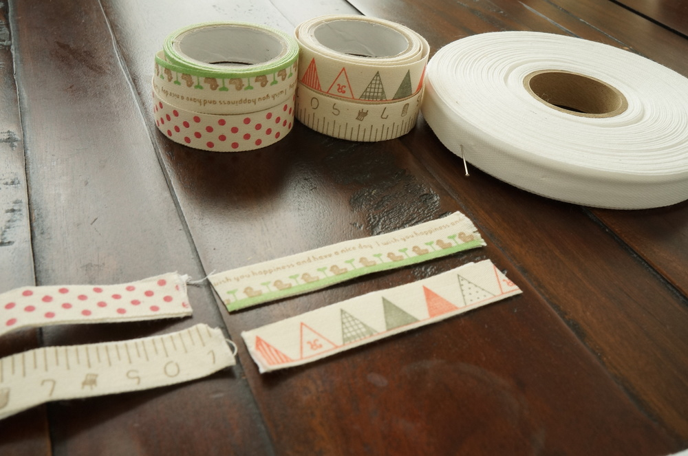 "Made tapes using a roll of twill tape, and cute ""scrapbook"" tapes with double-sided tape on the back. I just cut and taped them to be used for loops for the toys.  