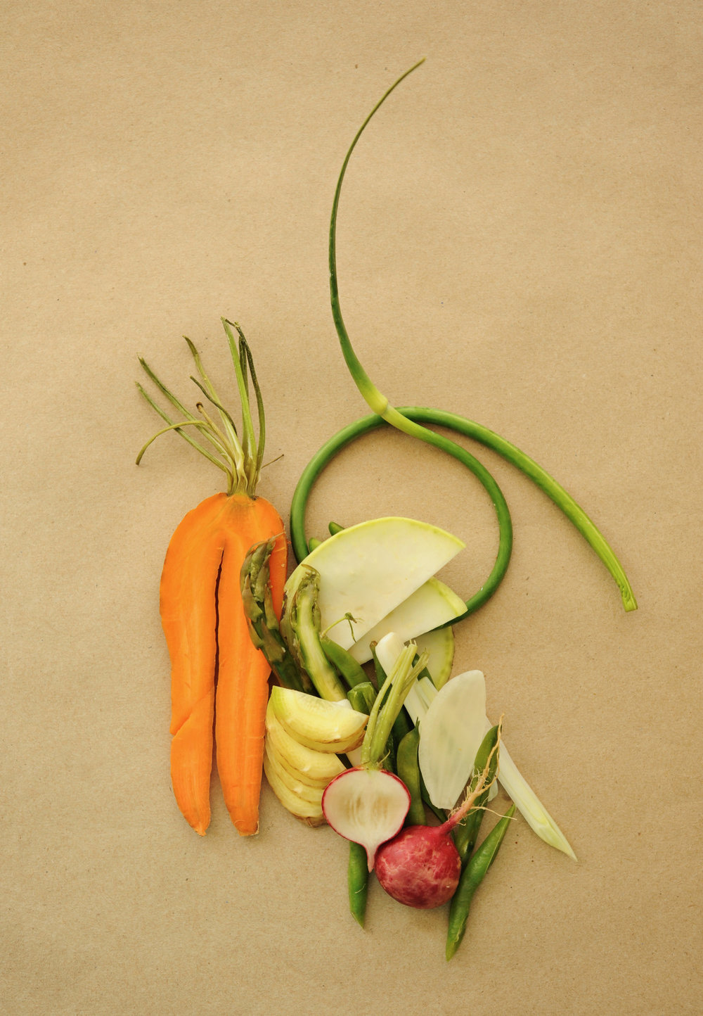 Photo by Marjorie Becker. Pictured: carrot legs, radishes, garlic scape, asparagus, onion, scallion, and green bean.