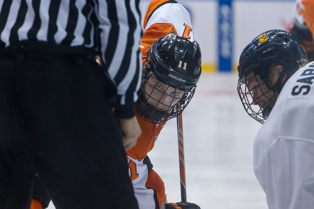 Andrew Miller, #11 Rochester Institute of Technology, left, waits for the puck to be dropped during a face-off at a semifinal Atlantic Hockey Conference hockey game against Canisius College at Blue Cross Arena on March 20, 2015 in Rochester, N.Y. RIT defeated Canisius 2-1 to advance to the championship game against Mercyhurst University.