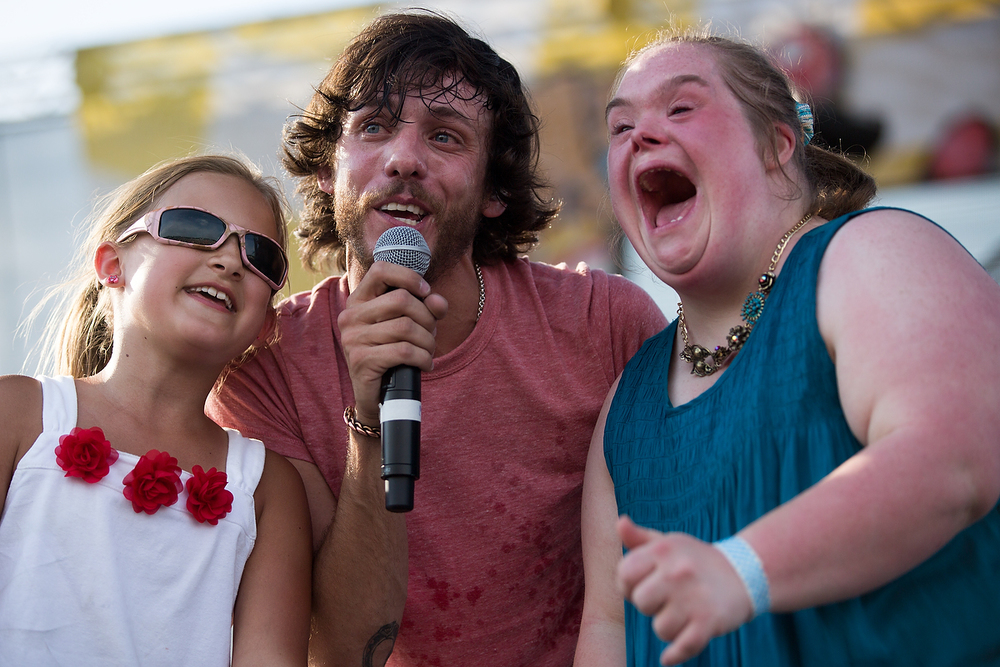 "Nikki Pelack, 10, of Martin, left, and Stephanie Russell, of Grand Ledge, right, sing with Chris Janson after being called on stage by Janson at the B-93 Birthday Bash 24 at US 131 Motorsports Park in Martin, Mich. Saturday, June 18, 2016. ""That is what it's all about,"" Janson said of bringing the girls on stage. B-93 Birthday Bash is a two day country music festival. (Bryan Bennett / Kalamazoo Gazette)"