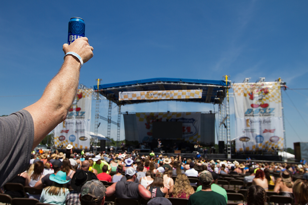 A man holds a Bud Light in the air as Lanco performs as the opening act of day one of the B-93 Birthday Bash 24 at US 131 Motorsports Park in Martin, Mich. Saturday, June 18, 2016. (Bryan Bennett / Kalamazoo Gazette)