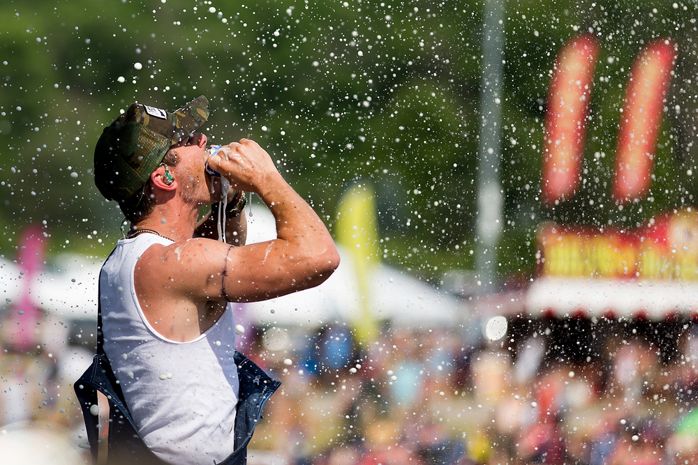 Granger Smith drinks two beers after smashing them together while performing at B-93 Birthday Bash 24 at US 131 Motorsports Park in Martin, Mich. during the first day of the country music festival on Saturday, June 18, 2016. (Bryan Bennett / Kalamazoo Gazette)