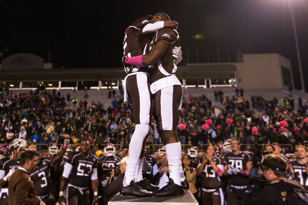 Western Michigan Broncos Carrington Thompson (15), left, and teammate Michael Henry (83) hug while leading the marching band after defeating Easter Michigan 45-31in a NCAA college football game at Waldo Stadium in Kalamazoo, Mich. on Saturday, Oct. 22, 2016. Thompson and Henry are also cousins. (Bryan Bennett | MLive.com)