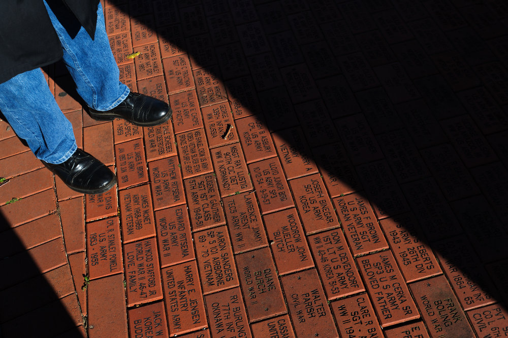 Jacob Rickli looks at bricks with names on them at Rose Park Veterans Memorial during the Kalamazoo County Veterans Day Ceremony in Kalamazoo, Mich., Friday, Nov. 11, 2016. (Bryan Bennett | MLive.com)