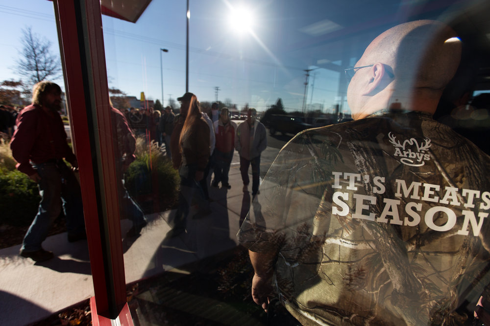 Dan Burch, general manager of Arby's in Plainwell, Mich., holds the door open for customers at 10 a.m., Saturday, Nov. 12, 2016. The sandwich's were sold out in less than 20 minutes. (Bryan Bennett | MLive.com)
