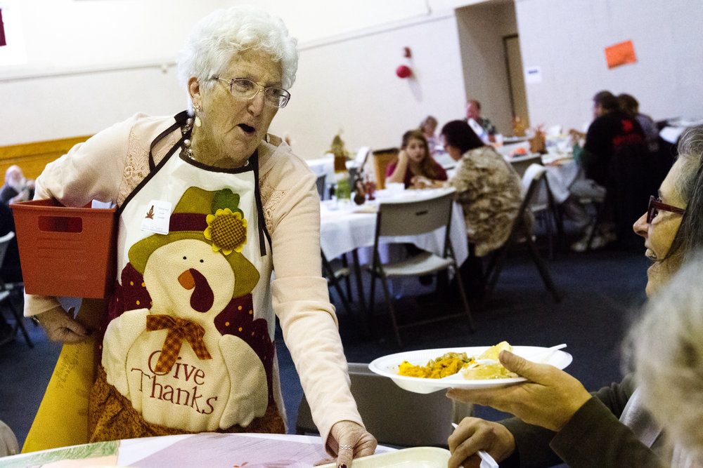 "Pat Cutts, 77, of Paw Paw, volunteers during the 32nd annual Paw Paw Community Thanksgiving Dinner at Freshwater Community Church in Paw Paw, Mich., Thursday, Nov. 24, 2016. ""I'm happy because I don't have to cook,"" Cutts said. Cutts has been volunteering for the past three years. Over 600 pounds, or 38 turkeys, were smoked for the annual dinner. (Bryan Bennett 