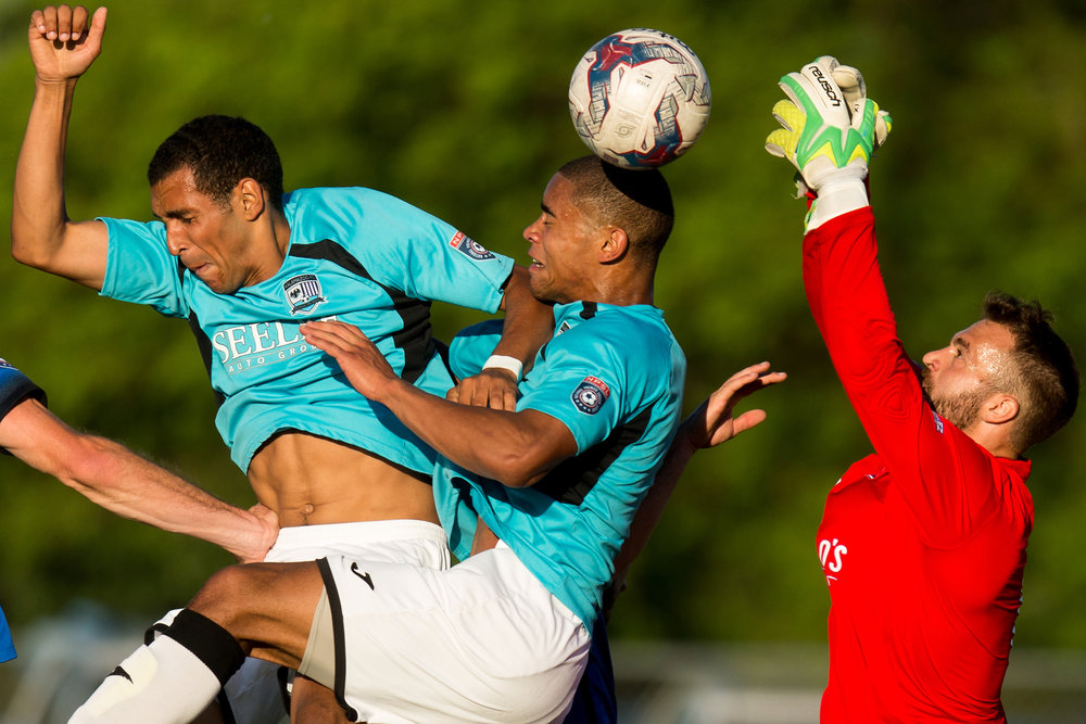 Kalamazoo FC's Corey Werner (14), Mattawan, left, and Brandon Bye (5), Portage, center, attempt to head the ball into the net as Grand Rapids FC's keeper Noah Fazekas (1) blocks it during an NPSL match at Mayors' Riverfront Park in Kalamazoo, Mich. on Sunday, June 5, 2016. Grand Rapids defeated Kalamazoo 2-0.