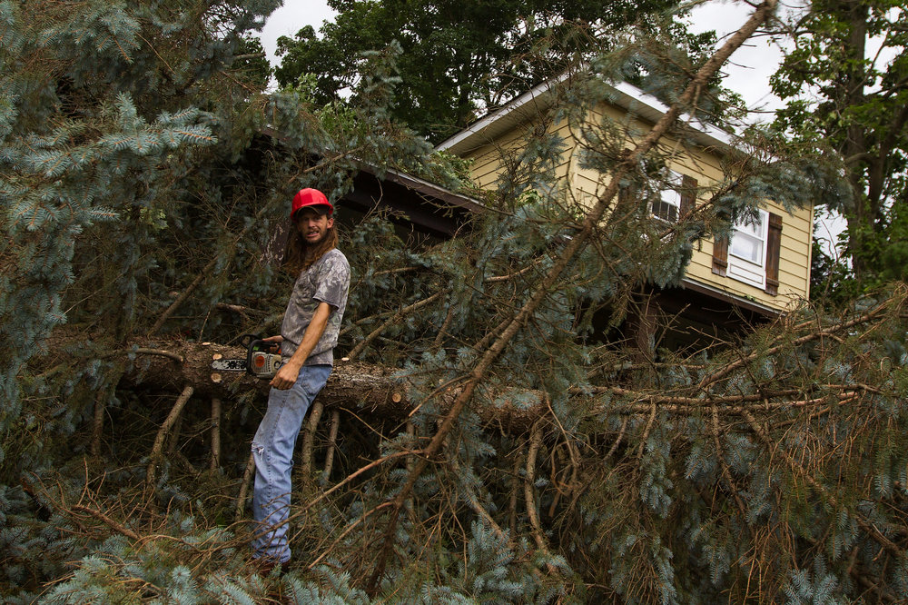 Lamar Sanford, 4 Seasons Tree Removal, works at a property Monroe St. and Division St. in Bangor, Mich. Sunday, Aug. 21, 2016. A tornado damaged homes throughout the area.