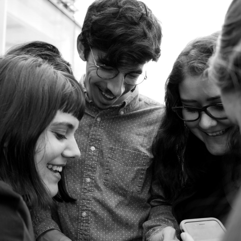 RIT students Dani Lyman, left, Joey Ressler, center, and JuliAnna Patino look at a cell phone picture on the sixth floor of the Newseum on Oct. 16, 2017 in Washington D.C.