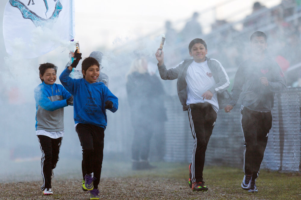 From left to right, David Gonzalez, 12, Eric Gonzalez, 11, Cristian Moreno, 11, and Lorenzo Moreno, 13, run down the side of Mayors' Riverfront Park soccer field with smoke during the second half of the NPSL soccer match between Kalamazoo FC and Lansing United Sunday, May 15, 2016, in Kalamazoo, Mich. The game resulted in a 0-0 tie. Jonah Hurtado, 13, is carrying the Kalamazoo FC flag at back. (Bryan Bennett / Kalamazoo Gazette)