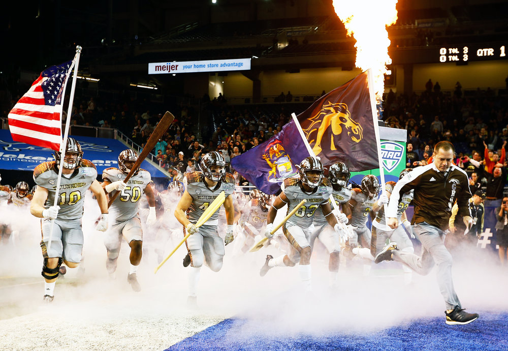 "The Broncos prepare to take on the Ohio Bobcats for the Mid-American Conference championship game at Ford Field in Detroit on Dec. 2, 2016. Bronco players rush the field carrying oars, a gesture symbolizing their mantra, ""Row the Boat."" Broncos' coach P.J. Fleck began the tradition following his son's death in 2011. He uses the saying to encourage his players to never give up."