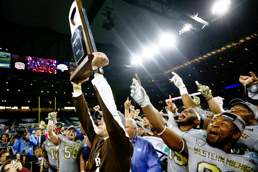 Broncos head coach P.J. Fleck, flanked by players, hoists the Mid-American Conference championship trophy after defeating the Ohio Bobcats 29-23.