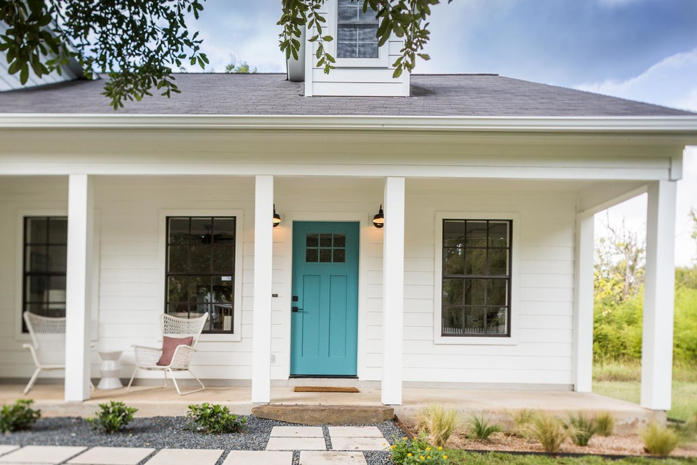 Modern East Austin Farmhouse with Turquoise Aqua Door, black windows, white siding, dormers, and native grasses.