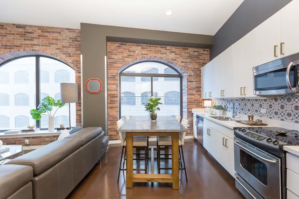 A counter-height island/dining table was added to add room for food prep or dining.  We love the bold, patterned backsplash. The gray, black and white compliment the gold pulls and freshly painted white cabinets. The bold pattern contrasts the brick.