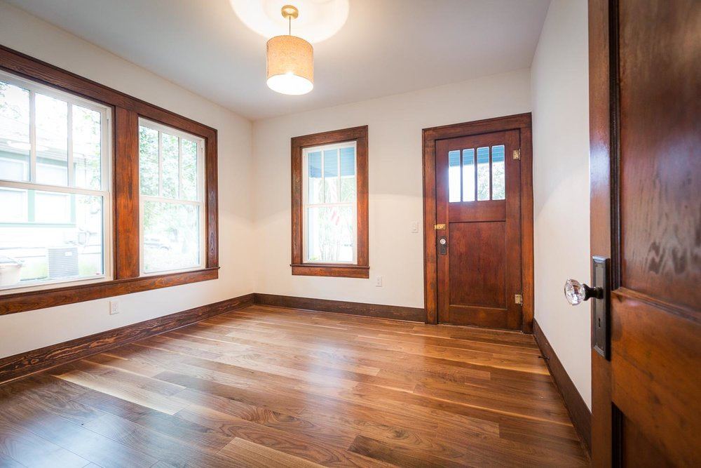 This room shows the beauty of the dark wood trim, new windows, walnut floors, original bronze hardware with (new) crystal door knobs, and natural light.