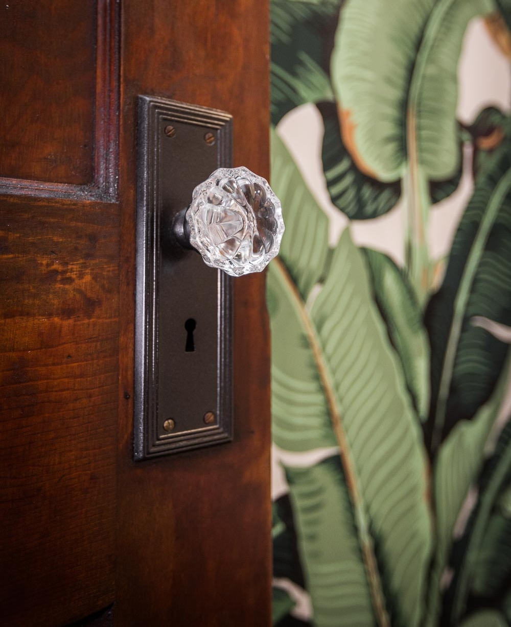 The old door plates were reused, but the crystal knobs are new. We refinished the old doors. The banana leaf wallpaper is hand printed.