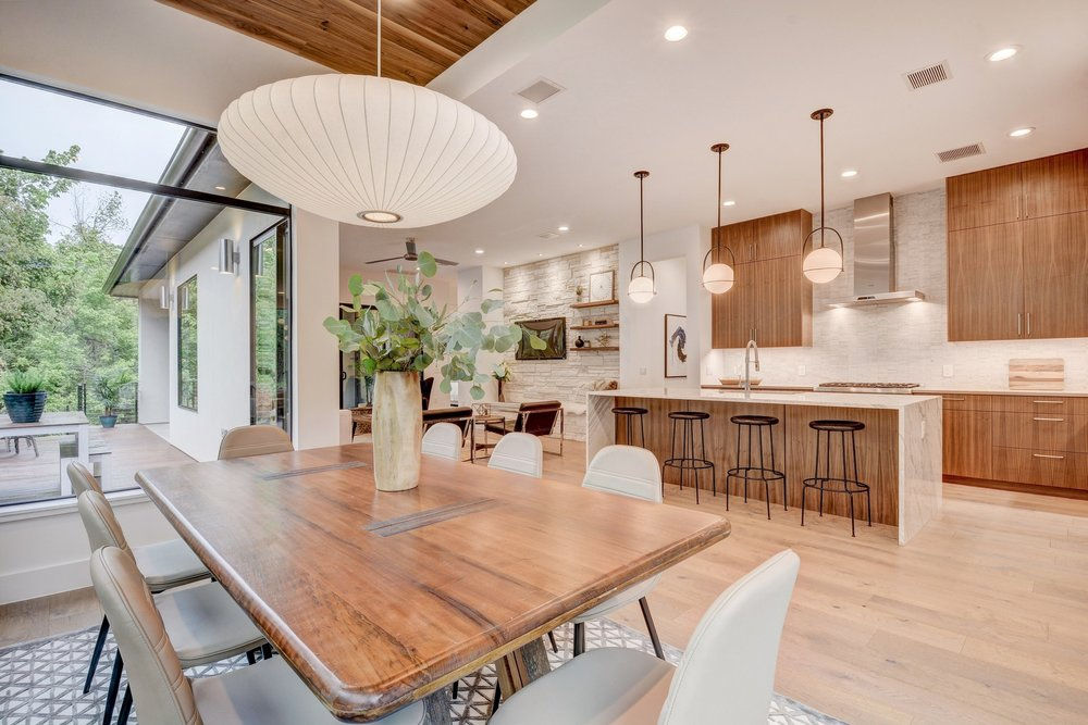 The dining room is a jewel box with three sides of glass, walnut wood ceiling, and a large Nelson bubble saucer pendant. It perfectly combines modern, classic, timeless, mid century, and transitional styles.
