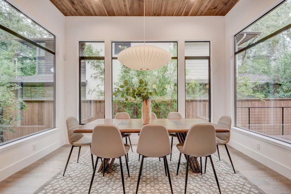 Modern dining room with Nelson pendant, glass walls, and wood ceiling.