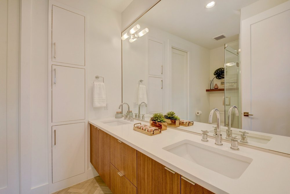 The second master bathroom includes white quartz countertops, cross bar faucets, and walnut cabinets.