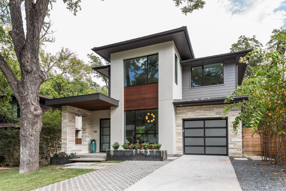 This exterior design was developed to appeal to both modern and traditional styles. We call it Modern Prairie Style. Ipe wood, stone masonry, stucco, Hardie, and a glass garage door, are assembled into a highend look for this narrow urban lot.