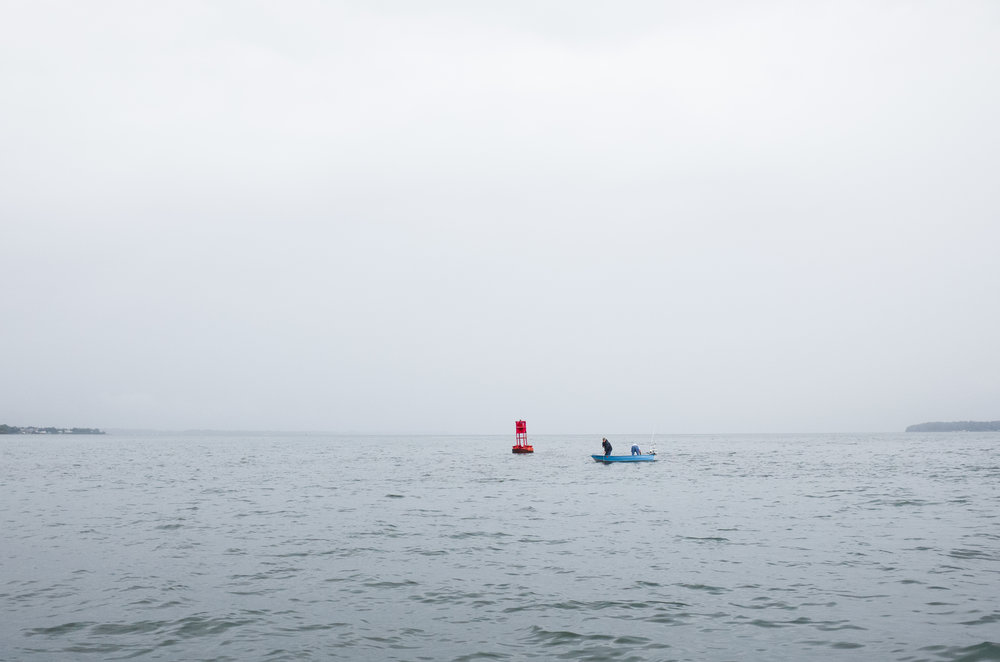 Two men scup fishing from a small dinghy amidst the morning fog.