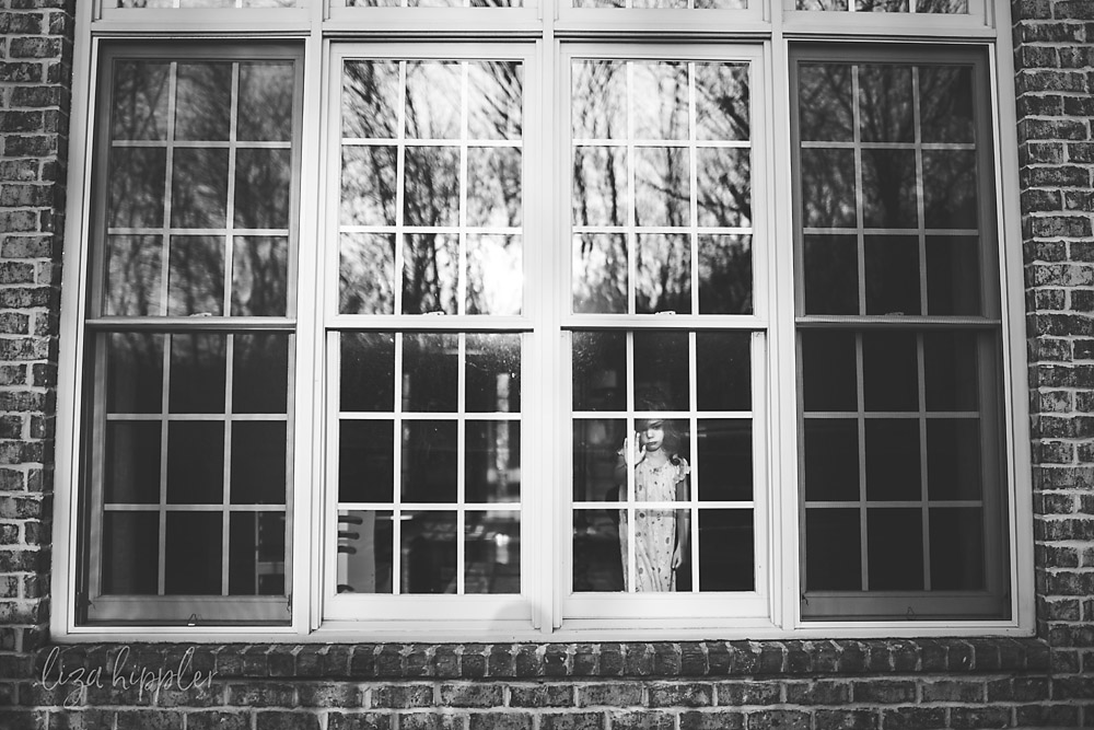 black and white image of little girl looking longingly out a large window