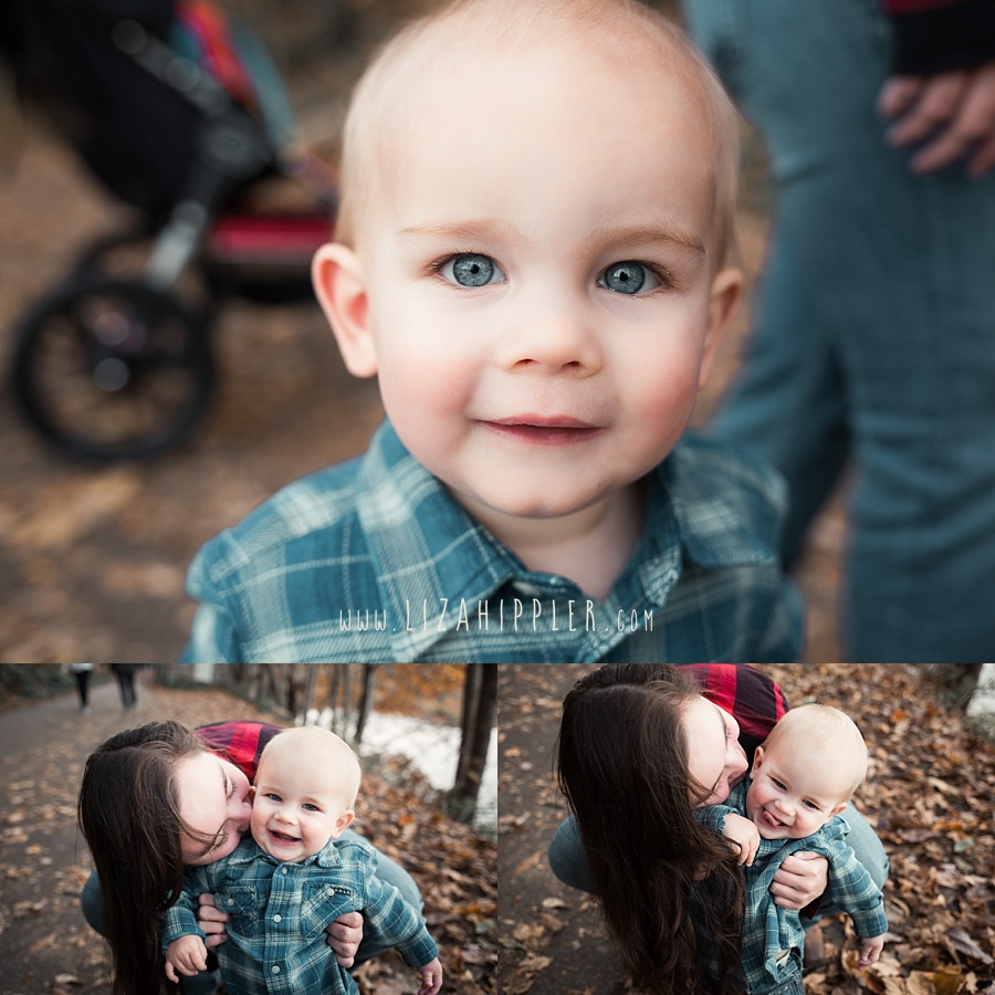 toddler boy with blue eyes looking at camera and playing with his mommy