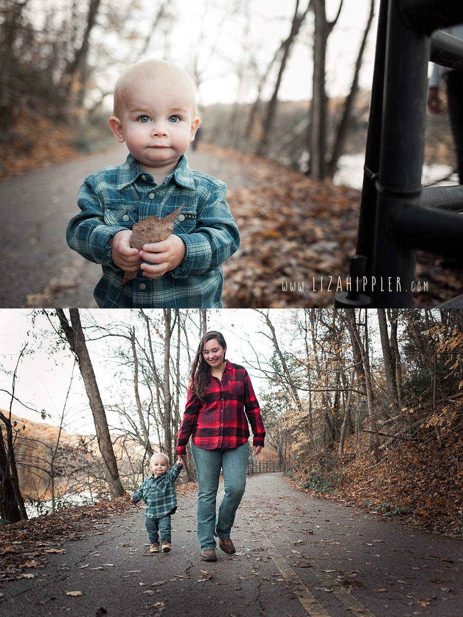 toddler boy with blue eyes walking on leaves and holding his mommy's hand