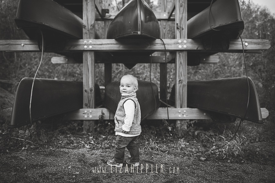 toddler boy in front of a rack of canoes in a black and white photo