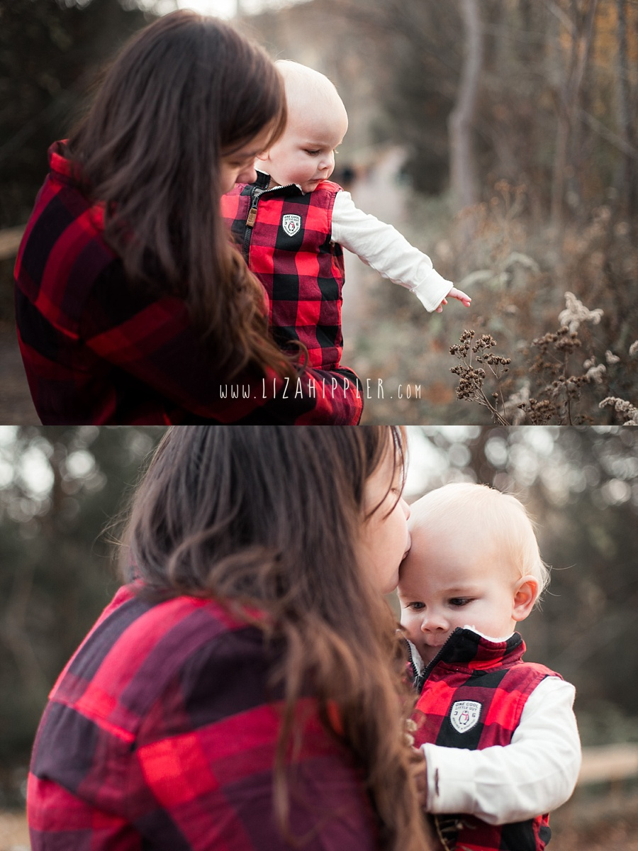 mother and toddler son wearing matching red plaid and getting smooches outside by fall plants