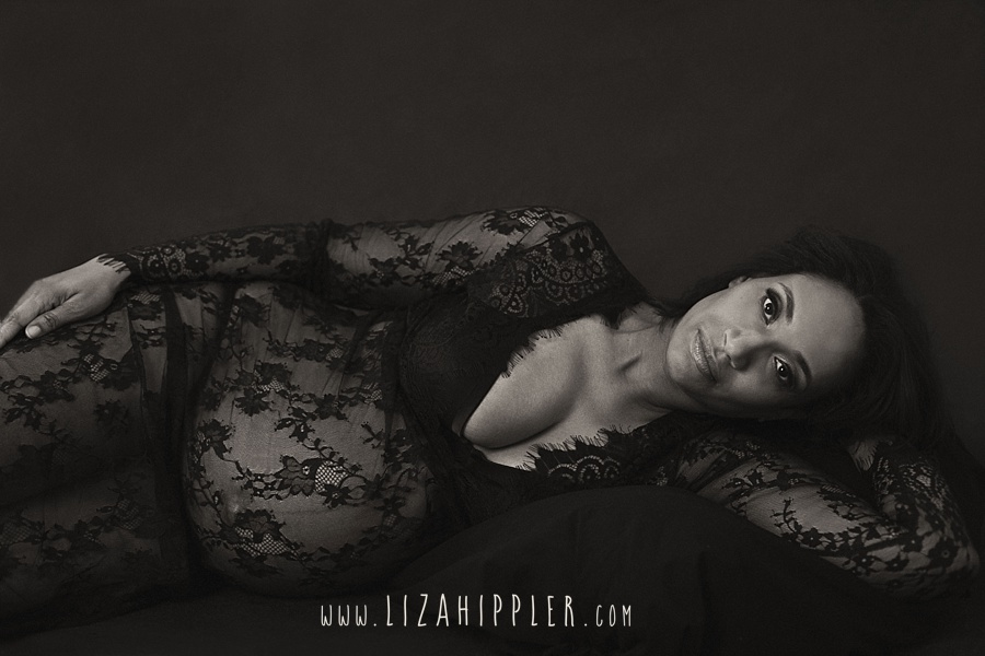 black and white maternity photo lying down in a black lace dress on a black background
