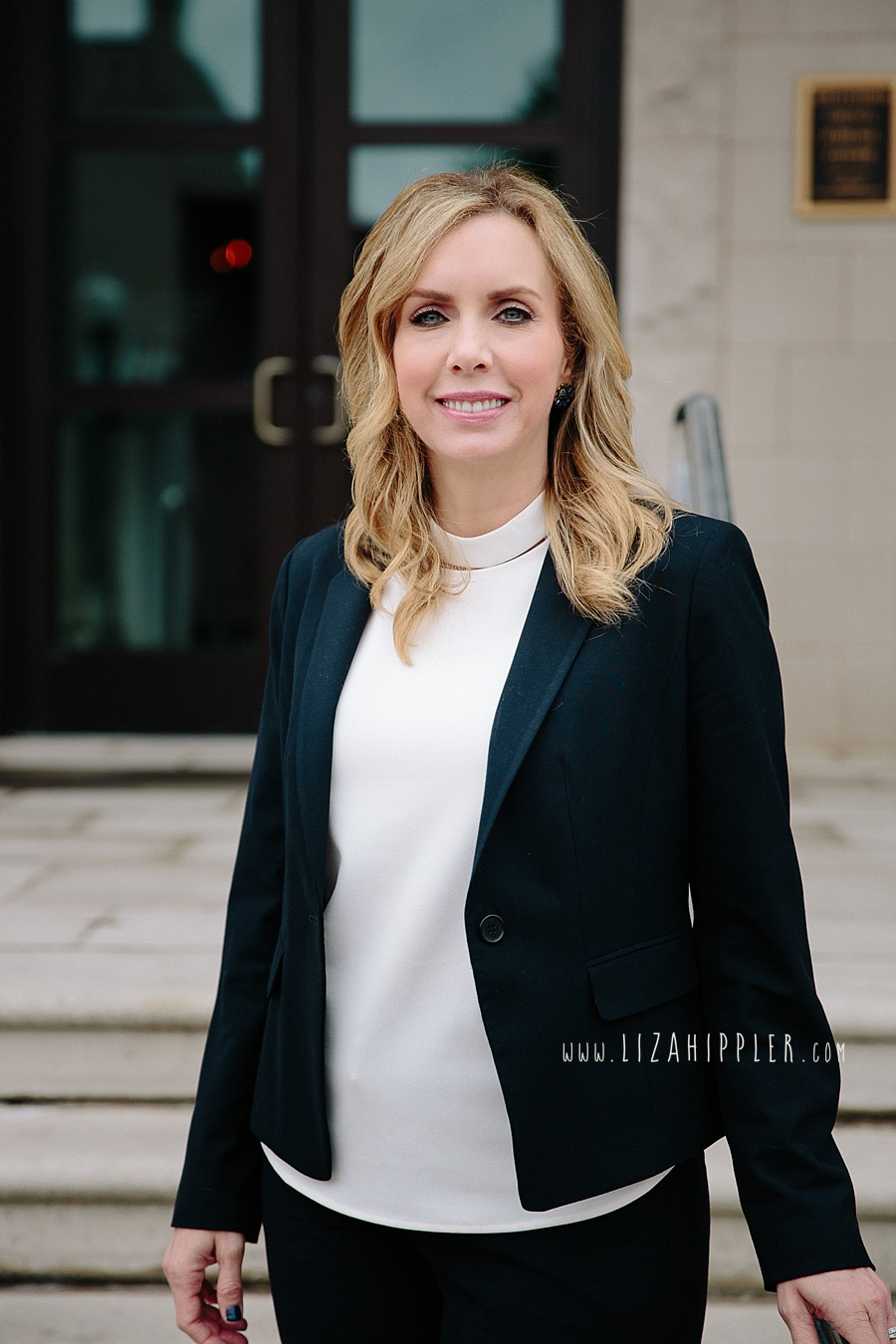 blonde blue-eyed female with white shirt and black blazer stands in front of Franklin tn courthouse