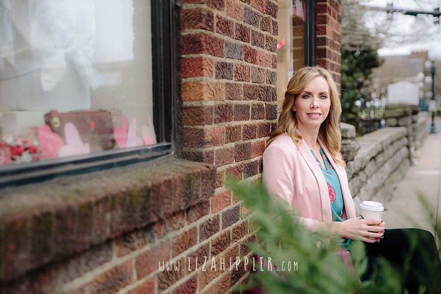 adult blonde female with blue eyes sits against a brick wall with a starbucks cup