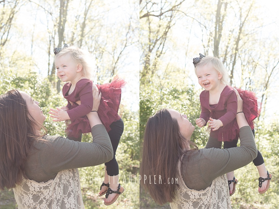 mom throwing baby girl in the air and catching her