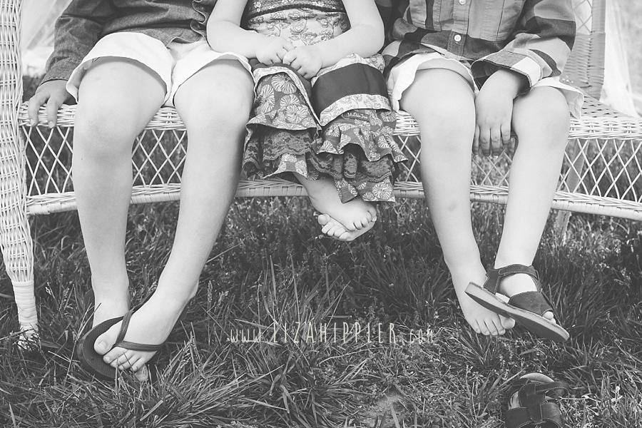 image of young kids feet hanging off a wicker bench