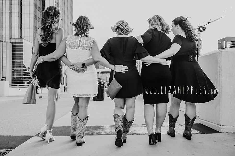 five ladies with their arms around each other walking down nashville pedestrian bridge