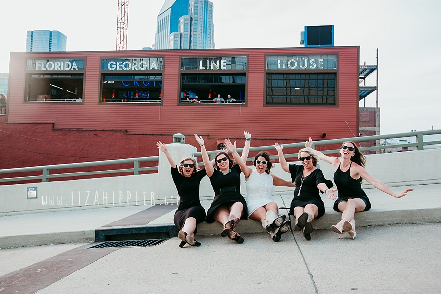 five ladies with their arms up sitting in front of Florida Georgia Line House celebrating bachelorette party