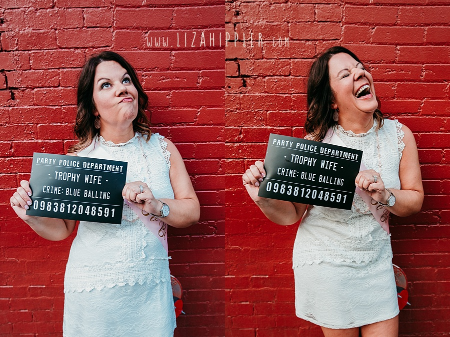 "bachelorette holding up ""trophy wife"" crime sign in front of red brick wall in Nashville"