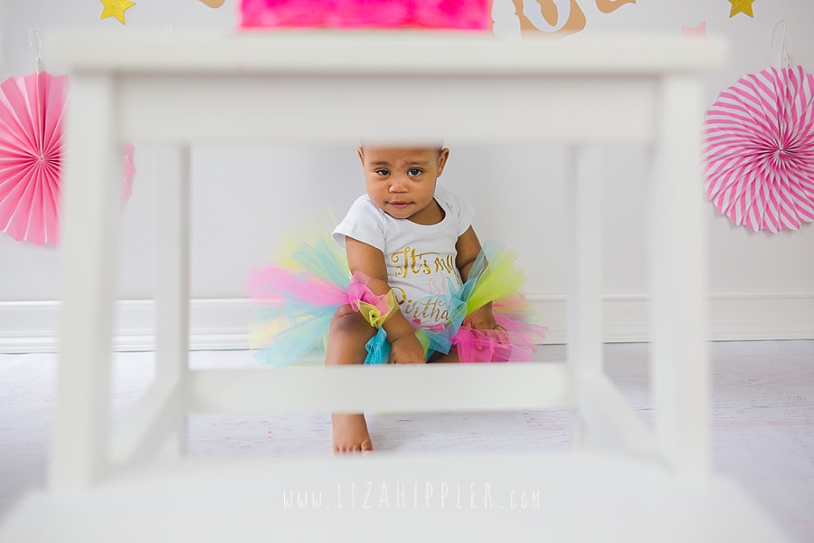 adorable baby girl peeks through stool legs in pink cake smash session