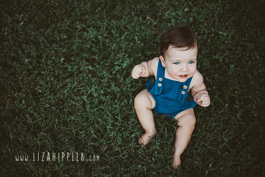overhead shot of baby boy in blue overalls in grass