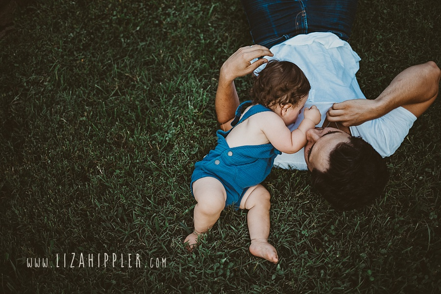 baby boy climbs on his dad in grass