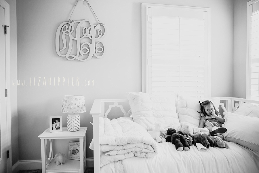black and white image of toddler girl in her beautiful bedroom