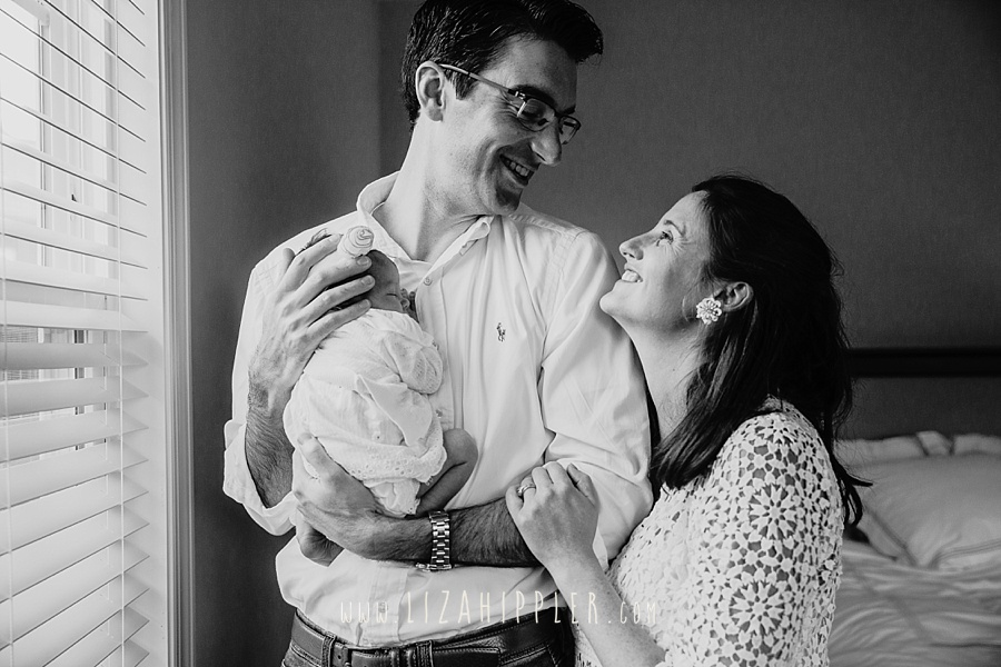 mom and dad smile at each other while holding newborn girl