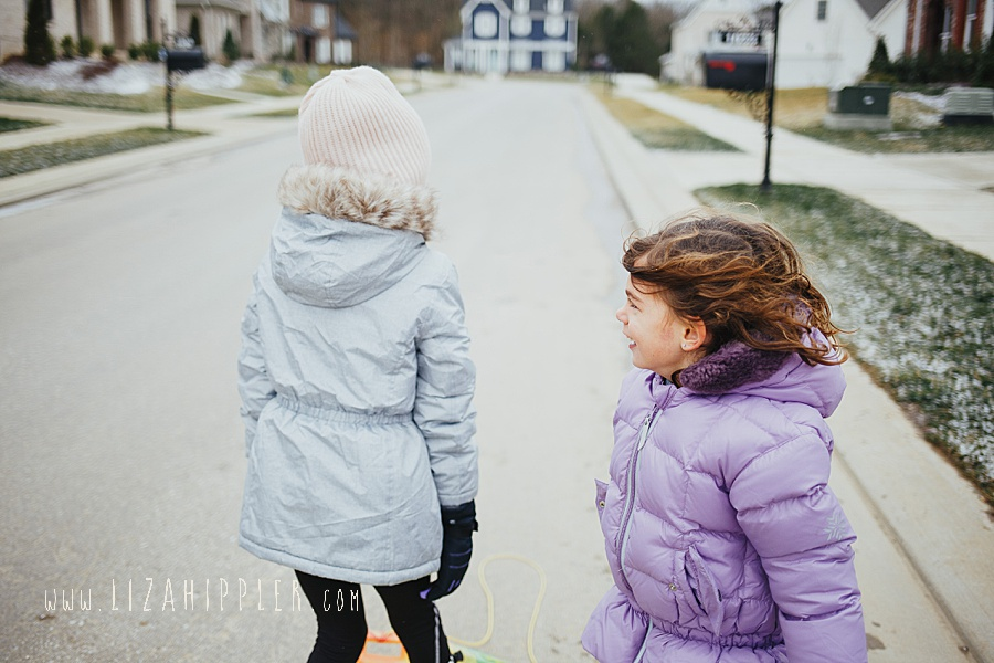 little sister in purple coat and big sister in grey coat