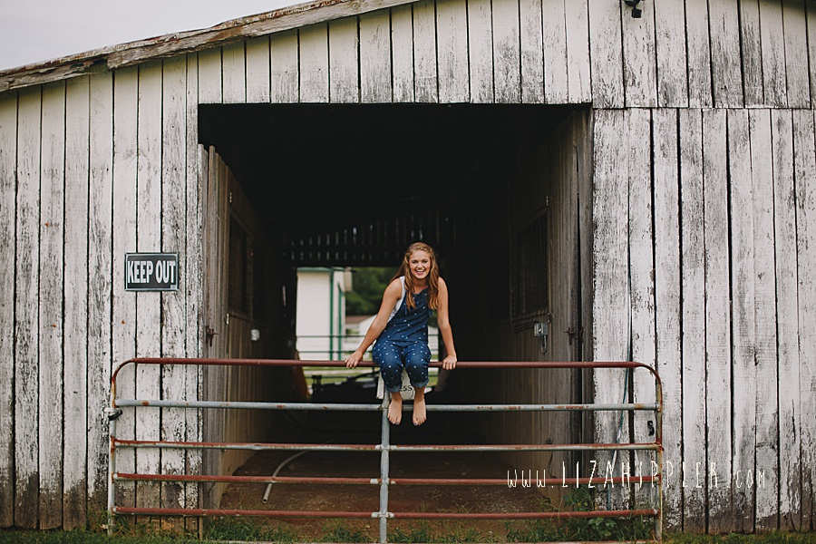 17 year old girl sits on fence by barn wearing overalls
